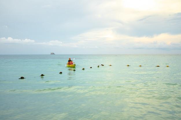 Kayakista remando el kayak en el mar