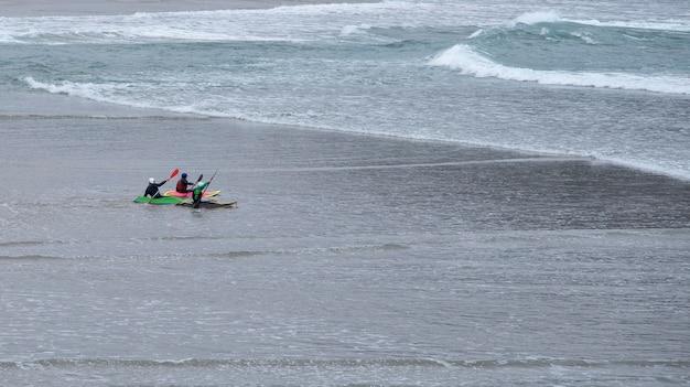 Kayakistas entrando al agua desde la arena