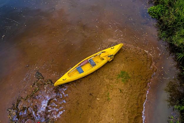 Kayaks y canoas vacíos multicolores en la orilla del río, vista de arriba hacia abajo
