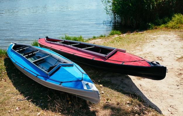 Kayaks vacíos en la orilla del río.
