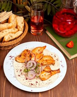 Kebab de alitas de pollo a la parrilla servido con composto, ensalada de cebolla y hierbas en un plato blanco