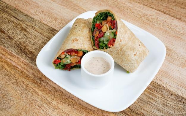Kebab con bebida envuelta en pan de pita con papas fritas y salsa de tomate. sirve los platos sobre tablas de madera.