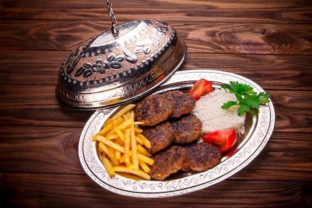 Kebab de carne con bolas de arroz y papas fritas.