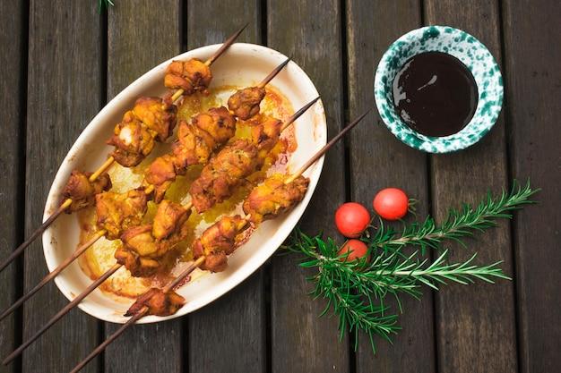 Kebab de carne servido con verduras y salsa