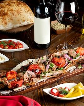 Kebab de carne sobre una baqueta con tomates envueltos en grasa
