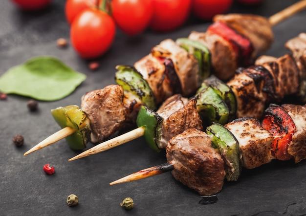 Kebab de cerdo y pollo a la parrilla con pimentón sobre tabla de cortar de piedra con sal, pimienta y tomates en negro. macro