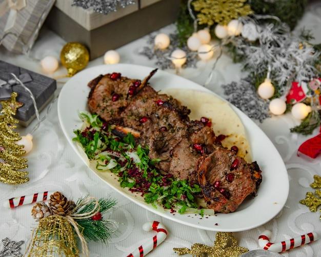 Kebab de cordero marinado en hierbas adornado con semillas de granada, cilantro y cebolla