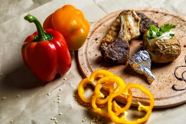 Kebab de costillas de cordero servido con patata sobre tabla de madera