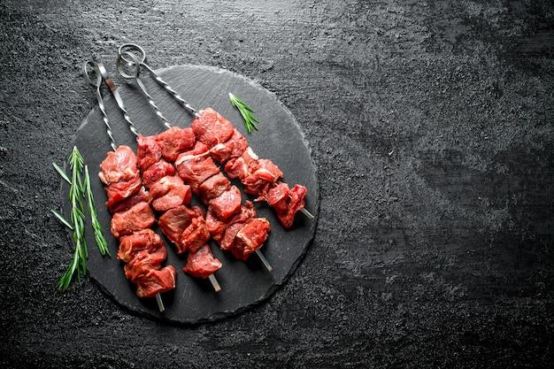 Kebab crudo con romero en mesa de madera negra