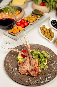 Kebab de entrecot servido con aceitunas encurtidos y copa de vino