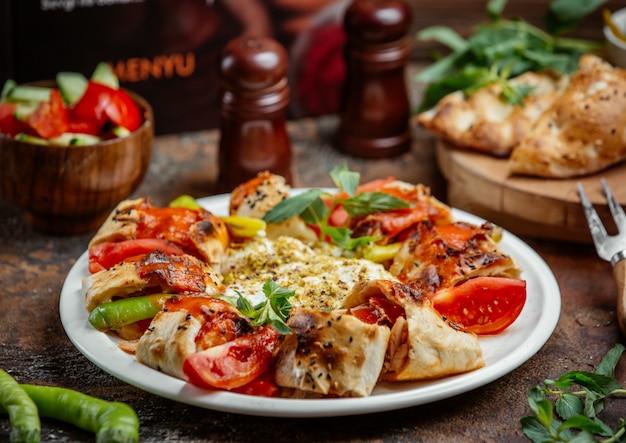 Kebab envuelto en beyti cubierto con salsa de tomate, servido con tomate, pimiento y yogur
