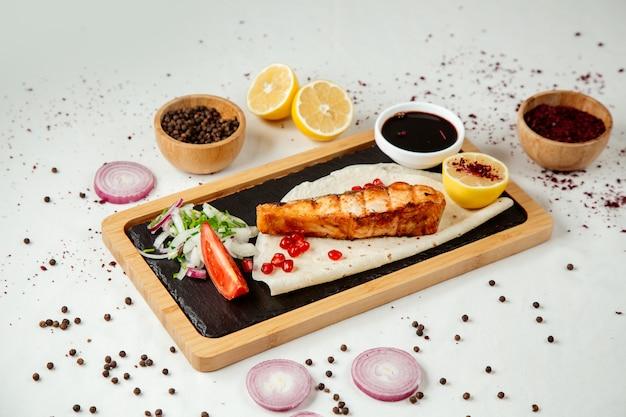 Kebab de pescado con cebolla narsharab sobre una plancha de madera