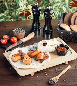 Kebab de pollo con lavash sobre tabla de madera