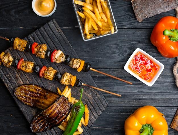Kebab de pollo con verduras con papas fritas sobre la mesa