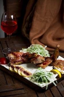 Kebab servido con cebolla picada, trozo de limón y vino tinto