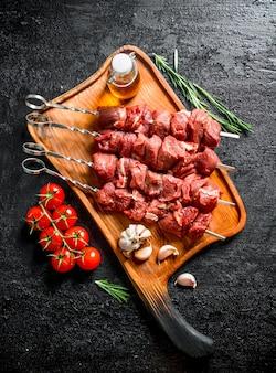 Kebab de ternera cruda en la tabla de cortar con tomates, ajo, romero y aceite en la mesa de madera negra