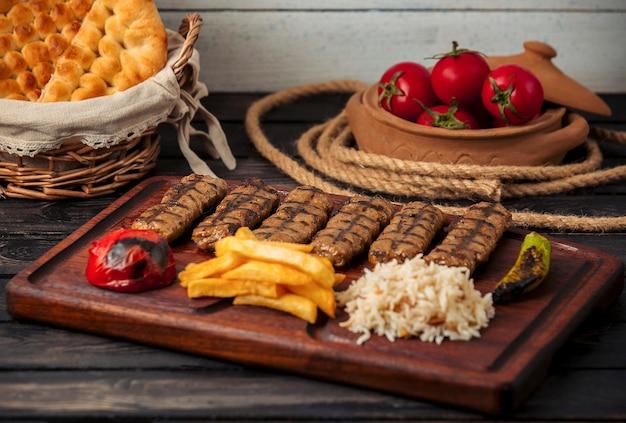 Kebabs de lula de res servidos con arroz, papas fritas, tomate a la parrilla y pimientos