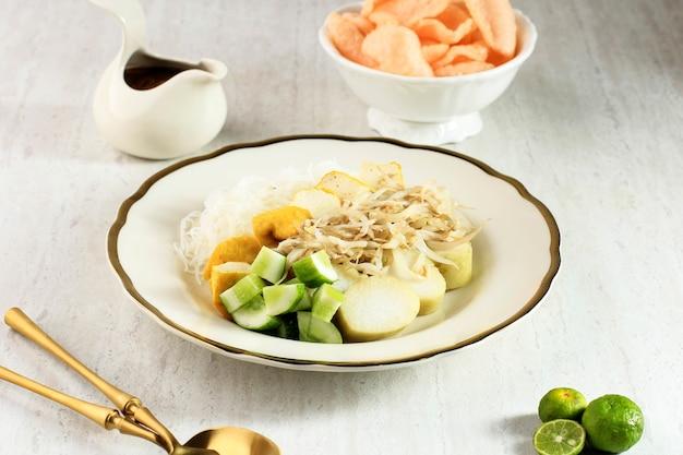 Ketoprak betawi. plato tradicional de comida callejera de pastel de arroz (lontong), fideos de arroz, cuajada de frijoles, huevo y brotes con aderezo de salsa de maní picante.