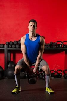 Kettlebell entrenamiento entrenamiento hombre en el gimnasio