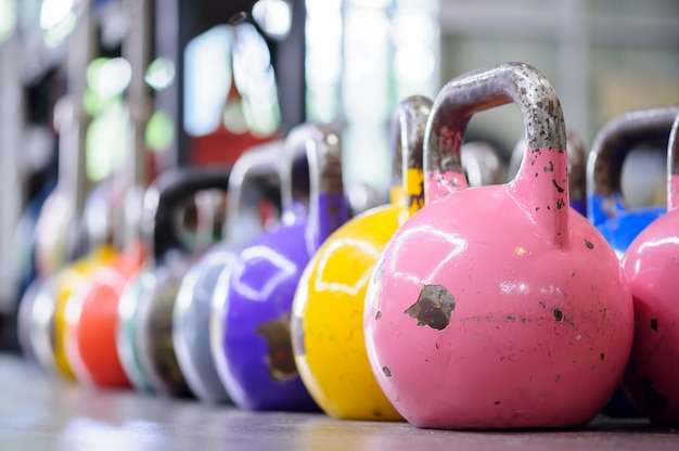 Kettlebells coloridos en una fila en un gimnasio