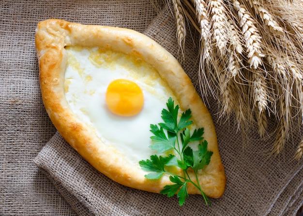 Khachapuri con huevo y perejil sobre tela de saco, espigas de trigo