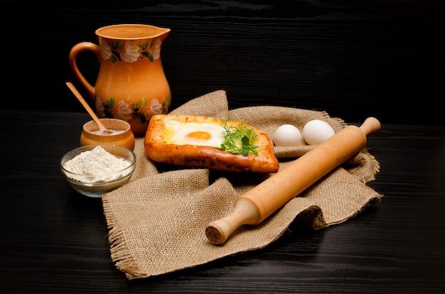 Khachapuri sobre tela de saco, rodillo, harina, huevos y jarra sobre un fondo negro