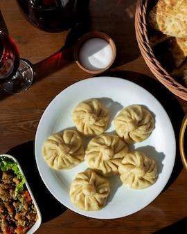 Khinkali con ensalada de carne, pan, compota y sal en la mesa