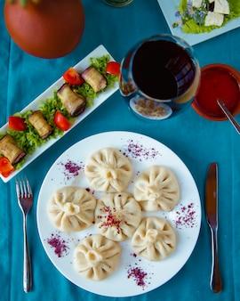 Khinkali servido con rollos de berenjena y copa de vino