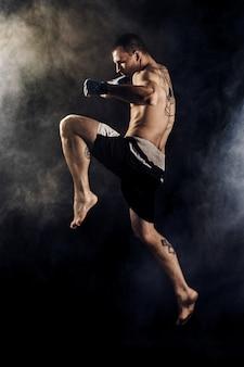 Kickbox muscular o luchador de muay thai golpeando en salto. fumar