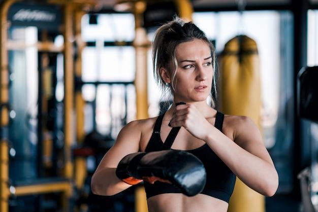 Kickboxer femenino joven que pone su guante de boxeo.