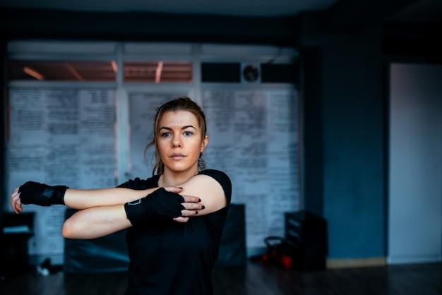 Kickboxer mujer estiramiento. de cerca.