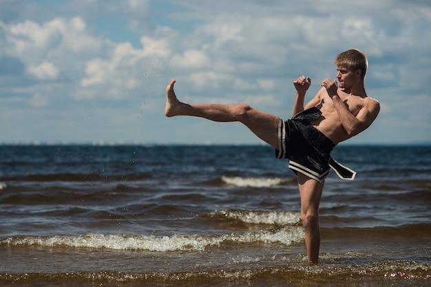 Kickboxer patea al aire libre en verano contra el mar.