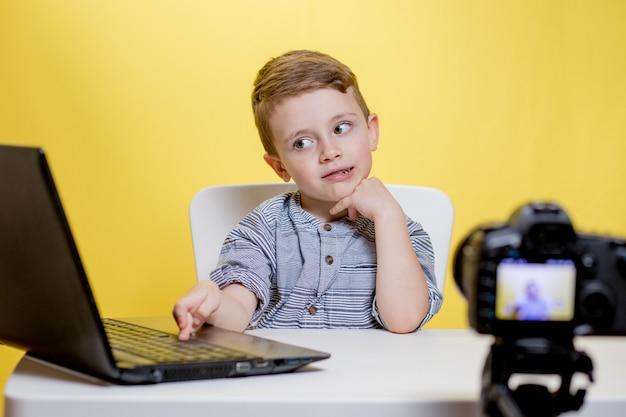 Kid blogger filmando video en la cámara trabajando con la computadora portátil