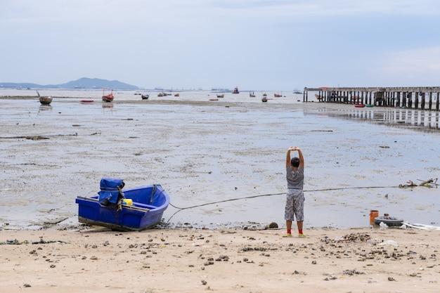 Kid boy jugando en la playa con pequeño bote de pesca