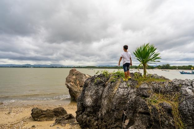 Kid boy de pie sobre las rocas en el parque forestal khao ta mong lai, prachuap khiri khan.