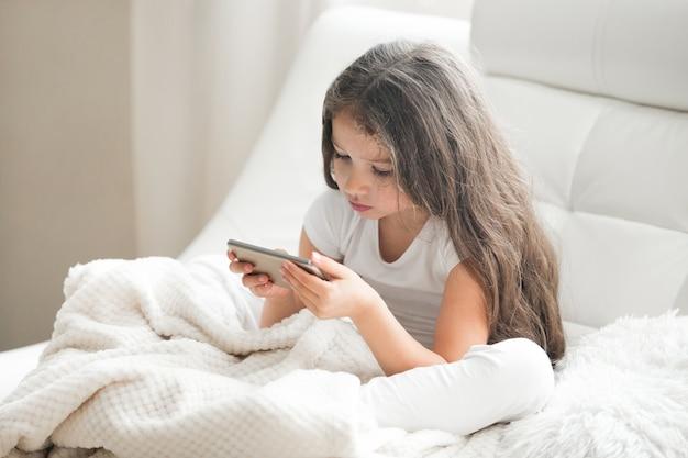 Kid chica jugando juegos en tableta en casa