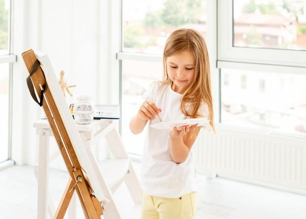 Kid niña dibujando con pintura al óleo y paleta