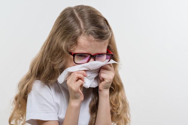 Kid niña estornuda en pañuelo