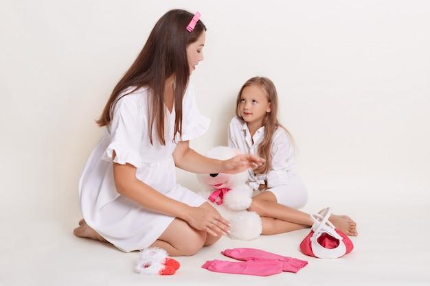 Kid niña y madre embarazada sentada en el piso rodeado de ropa infantil
