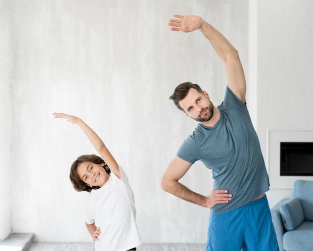 Kid y su padre haciendo deporte en casa