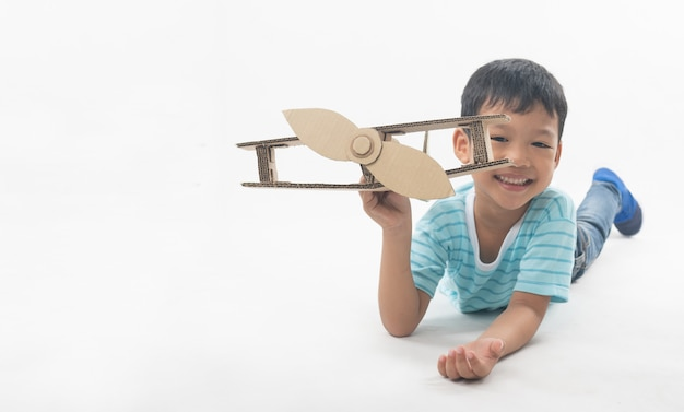 Kid sueña como piloto tendido y sosteniendo papel de avión
