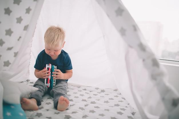 Kid está tendido en el suelo. niño está jugando en casa con coches de juguete en casa por la mañana. estilo de vida informal en el dormitorio.