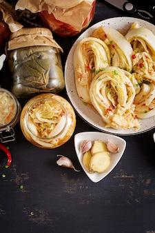 Kimchi de col, tomates marinados, frascos de vidrio agrio de chucrut sobre la mesa de la cocina rústica.