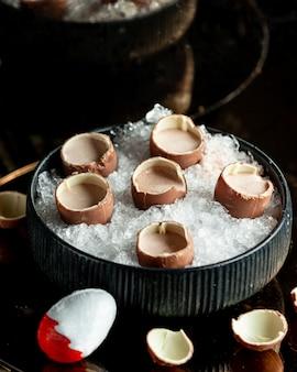 Kinder sorpresa con cacao en un recipiente con hielo