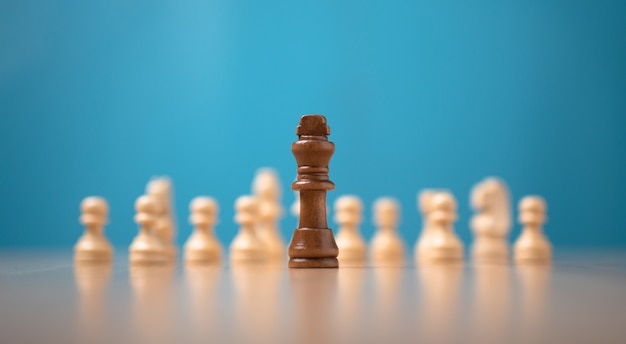 King brown ajedrez parado frente al ajedrez blanco, concepto de desafío en la competencia