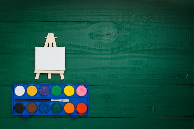 Kit de acuarela y caballete en miniatura sobre fondo verde