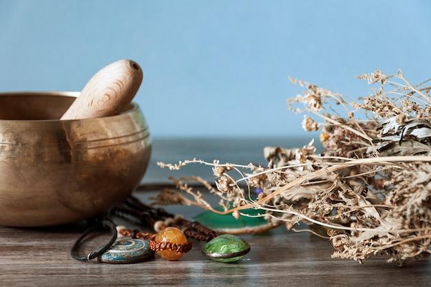 Kit de bruja sobre una mesa de madera hay un cuenco de metal amarillo, cristales verdes y naranjas y hierbas secas.