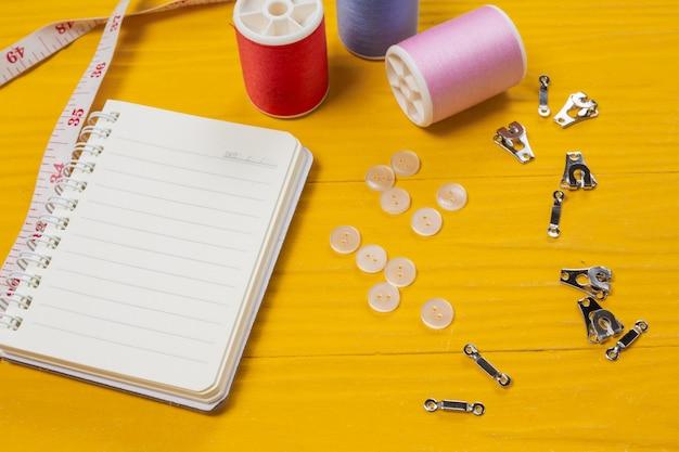 Un kit de costura, aguja, hilo, una aguja, colocada sobre un piso de madera amarillo.