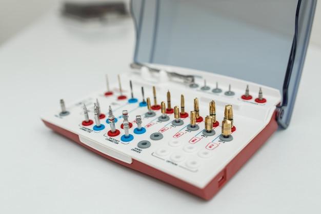 Kit de herramientas de prótesis dental sobre fondo blanco.