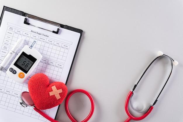 Kit de prueba de estetoscopio, corazón rojo y azúcar en la sangre en la pared gris.